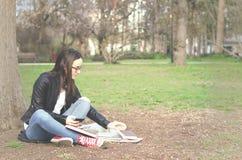 Escuela o estudiante universitaria joven hermosa con el pelo largo, los vidrios y la chaqueta de cuero negra sentándose en la tie Fotos de archivo libres de regalías
