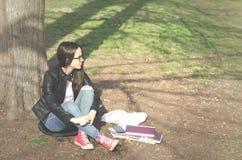 Escuela o estudiante universitaria joven hermosa con el pelo largo, los vidrios y la chaqueta de cuero negra sentándose en la tie Imagen de archivo