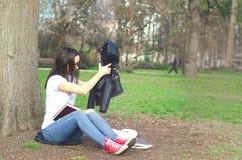 Escuela o estudiante universitaria joven hermosa con los vidrios largos del pelo y del ojo que se sientan en la tierra en el parq Fotografía de archivo libre de regalías