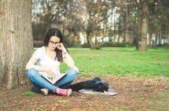 Escuela o estudiante universitaria joven hermosa con los vidrios largos del pelo y del ojo que se sientan en la tierra en el parq Imagen de archivo libre de regalías