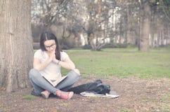 Escuela o estudiante universitaria joven hermosa con los vidrios largos del pelo y del ojo que se sientan en la tierra en el parq Imágenes de archivo libres de regalías