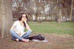 Escuela o estudiante universitaria joven hermosa con los vidrios largos del pelo y del ojo que se sientan en la tierra en el parq Foto de archivo