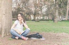 Escuela o estudiante universitaria joven hermosa con los vidrios largos del pelo y del ojo que se sientan en la tierra en el parq Fotos de archivo libres de regalías
