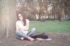 Escuela o estudiante universitaria joven hermosa con los vidrios largos del pelo y del ojo que se sientan en la tierra en el parq Foto de archivo libre de regalías