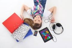 Escuela y concepto del entretenimiento - adolescente que miente con la tabla Imágenes de archivo libres de regalías