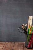 Escuela y materiales de oficina en la tabla de la sala de clase Foto de archivo libre de regalías