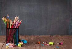 Escuela y materiales de oficina en la tabla de la sala de clase Imágenes de archivo libres de regalías