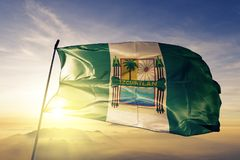 Escuintla Department of Guatemala flag textile cloth fabric waving on the top sunrise mist fog. Beautiful royalty free stock image