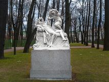 Esculpa Amur y la psique en el jardín del verano del parque en abril adentro Imagen de archivo libre de regalías