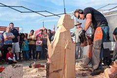Escultor Carves Dog Out da serra de cadeia da madeira Imagem de Stock Royalty Free
