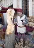 Escultor que talla una escultura de una mujer en un woode Foto de archivo
