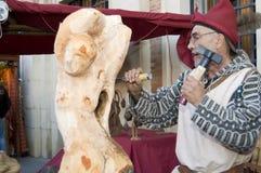Escultor que talla una escultura de una mujer en un woode Foto de archivo libre de regalías