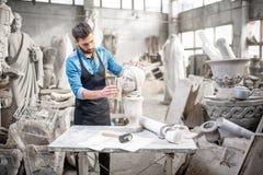 Escultor que trabaja con la escultura en el estudio imagenes de archivo