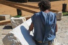 Escultor que trabaja un bloque de piedra con un cincel Imagen de archivo libre de regalías