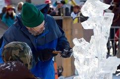 Escultor y ayudante del hielo en el carnaval del invierno Fotos de archivo