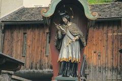 Escultura antiga de um homem com a cruz Imagens de Stock Royalty Free