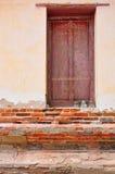 Escultura antiga do bhudda que senta-se perto das janelas fotos de stock