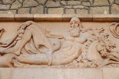 Escultura bonita antiga do bas-relevo no estilo do grego clássico da parede O deus Poseidon, doador dos povos molha imagem de stock royalty free