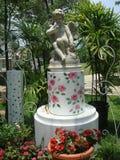 Escultura con las flores que pintan bajas en el jardín Fotografía de archivo libre de regalías
