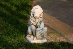 Escultura concreta del escudo poderoso de la tenencia del león en el borde de la trayectoria concreta rodeado con la hierba en dí foto de archivo