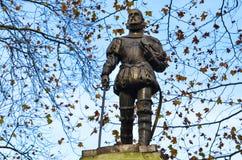 Escultura contra el cielo azul claro rodeado por los árboles del otoño con las hojas de la oscuridad marchitadas Foto de archivo libre de regalías