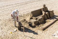 Escultura da areia do viajante na praia Foto de Stock