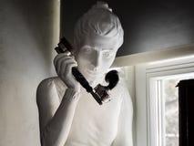 Escultura da mulher que guarda o monofone de telefone preto retro Imagem de Stock