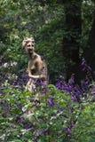 Escultura da ninfa entre plantas da alfazema na flor Imagem de Stock Royalty Free
