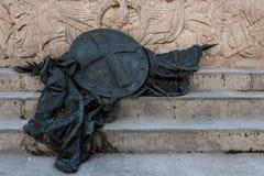 Escultura de bronce de un escudo y de una bandera caida en pasos Imagen de archivo