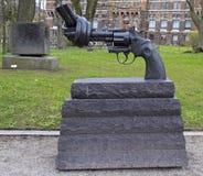 Escultura de bronze do revólver desproporcionado com um tambor atado Imagem de Stock