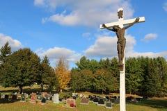 Escultura de bronze de Jesus Christ na cruz de madeira branca no cemitério fotografia de stock royalty free