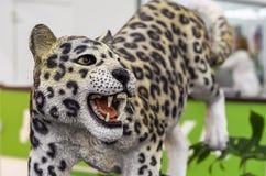 Escultura de cerámica grande de un jaguar en un fondo blanco-verde fotografía de archivo libre de regalías