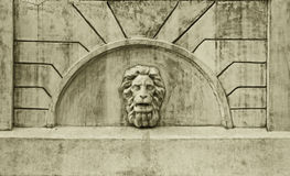 Escultura de la cabeza de un león en la pared vieja Imagen de archivo libre de regalías