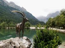 Escultura de la cabra de montaña - símbolo de Julian Alps cerca del lago artificial al norte de Krajnska Gora imagenes de archivo