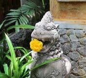 Escultura de la deidad con una flor Foto de archivo libre de regalías