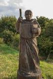 Escultura de madera del monje en un prado Imagen de archivo libre de regalías