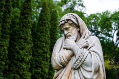 Escultura de mármol del parque de un viejo hombre que congela y envuelto en las sobrecamas que personifican la estación fría del  Fotos de archivo libres de regalías