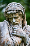 Escultura de mármore do parque de um ancião que congela-se e envolvido nas cobertas que personificam a estação fria do ano O palá Foto de Stock