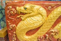 Escultura de oro de la serpiente en la pared del santuario Imagen de archivo