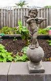 Escultura de pedra de um anjo pequeno que guarda uma decoração do jardim do instrumento do violino fotos de stock