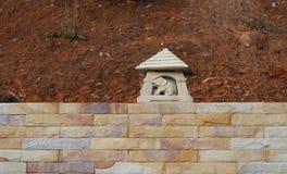 Escultura de un elefante en una pared de ladrillo Foto de archivo libre de regalías