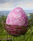 Escultura de un huevo de Pascua rosado gigante en una cesta fotos de archivo