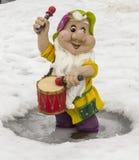 Escultura de un pequeño gnomo con un tambor fotografía de archivo