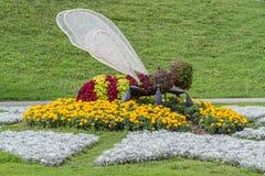 Escultura de una abeja en una cama de flores Imagen de archivo