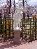 Escultura de una mujer con una guirnalda de rosas en el verano del parque Foto de archivo libre de regalías