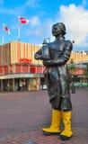 Escultura del granjero en el jefe del queso en sus manos Foto de archivo