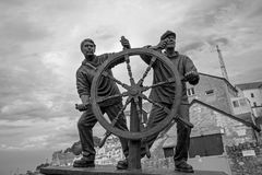 Escultura del hombre y del muchacho en el puerto de Brixham Foto de archivo libre de regalías