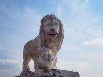 Escultura del león de piedra blanco en la orilla del río contra el cielo azul fotografía de archivo