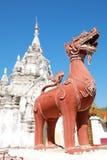 Escultura del león delante de Phra ese Hariphunchai Worramahawihan fotos de archivo