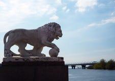 Escultura del le?n de piedra blanco en la orilla del r?o en el parque de la ciudad imagenes de archivo